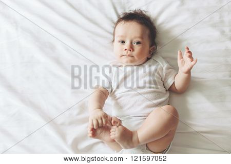 Portrait of a cute 4 months old baby lying down on a bed, top view