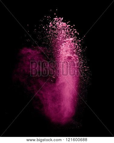 Explosion of pink powder on black background