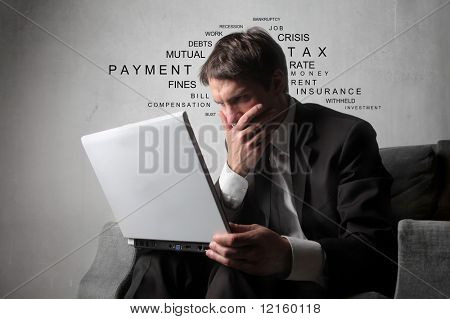 Businessman sitting on an armchair with a laptop and thinking