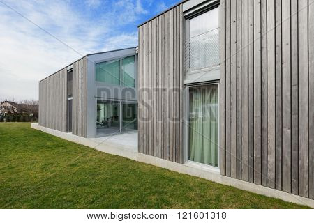 Exterior of a modern house in cement and wood, lawn
