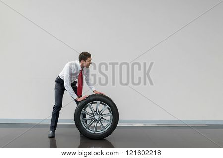 Young seller with wheel of car
