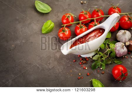 Tomato sauce in a sauce boat with fresh ingredients, including tomatoes, basil, garlic and spices. Food background, copyspace