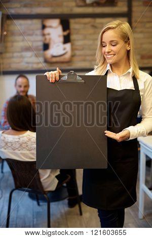 Attractive blonde waitress holding blank blackboard.