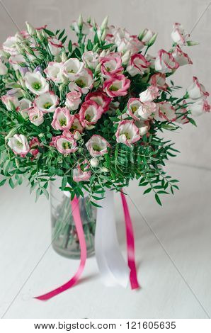 Beautiful romantic bouquet of pink and white eustoma flowers with satin tape in a vase on a white ba