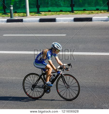 Female cyclist rides a racing bike on road