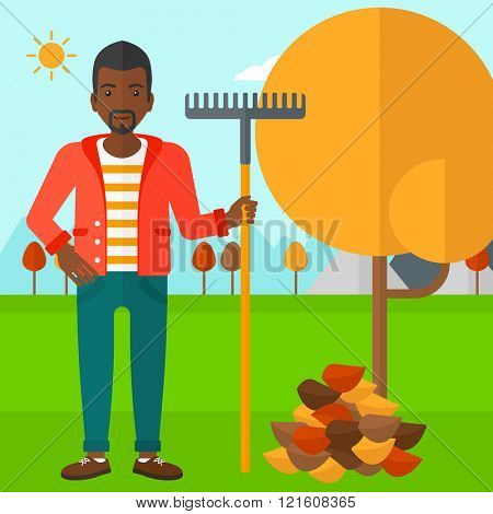 Man with rake near tree and heap of leaves.