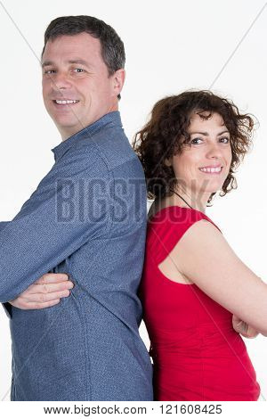 Cheerful Couple Sitting With Back Standing And Smiling Happily