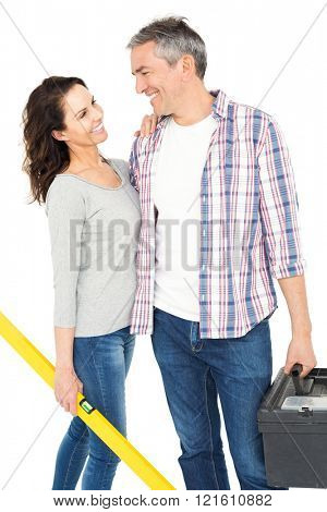 Couple with toolbox and bubble level on white background