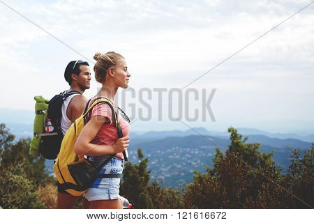 Young man and woman travelers are enjoying amazing nature view during their backpacking two hikers with rucksacks are resting after active walking in mountains during their summer weekend overseas