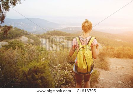 Back view of a young woman traveler with yellow rucksack is enjoying beautiful landscape during her hike blonde female wanderer is looking away while is standing on a high mountain in warm summer day