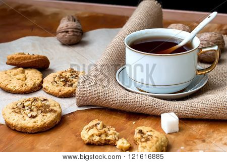 homemade shortbread cookies with nuts and a cup of strong black tea on the table