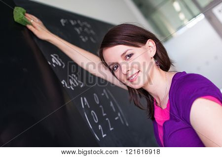 Pretty, young college student wiping the chalkboard/blackboard between classes (shallow DOF; color toned image)