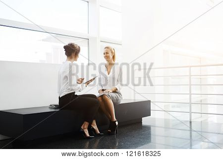 Young female lawyer is holding touch pad and talking something to her smiling client while they are sitting in modern office interior. Smart woman using digital tablet for consultation with customer