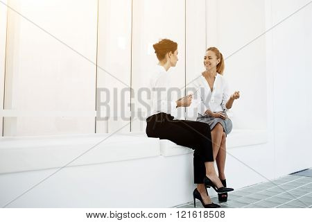 Smiling businesswoman is listening funny story of her partner which sitting near with portable touch pad in hands. Two female professional workers are having pleasant conversation during break at job