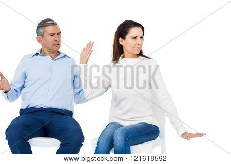 Couple arguing while sitting against white background