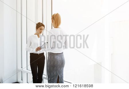 Young woman manager is reading from digital tablet for her boos results of their new projects abroad. Female secretary is searching information on touch pad for CEO while they are standing in office