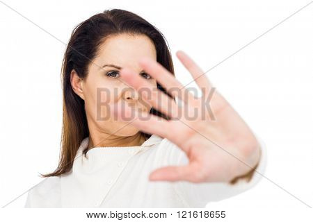 Unhappy woman hiding her face with hand against white background