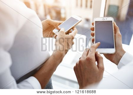 Two female are using cellphones