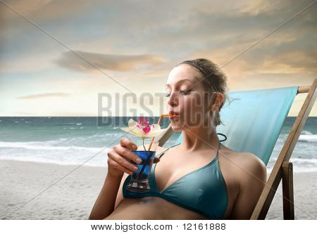 Beautiful woman lying on a deckchair at the seaside and drinking a cocktail