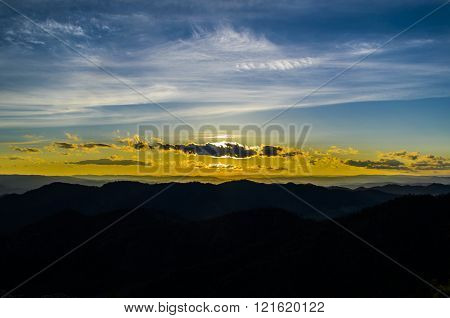 Sunset in the vast Siberian expanse and the silhouettes of the mountains