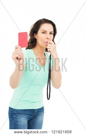 Mature woman blowing whistle and holding red card against white background