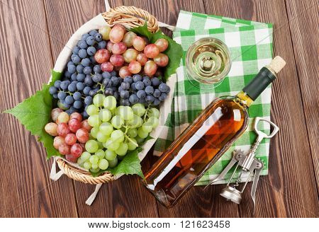 Bunch of grapes, white wine and corkscrew on wooden table background. Top view