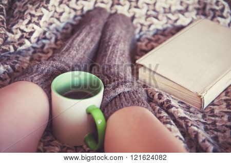 Woman Legs In Woolen Socks With Book And A Cup Of Tea