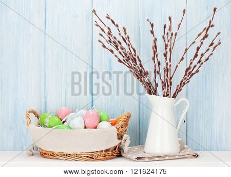 Pussy willow branches bouquet and colorful easter eggs on shelf in front of wooden wall. View with copy space