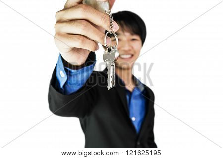 Businessman holding keys with smiling face, selective focus isolated on white background