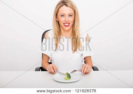 Happy woman eating broccoli