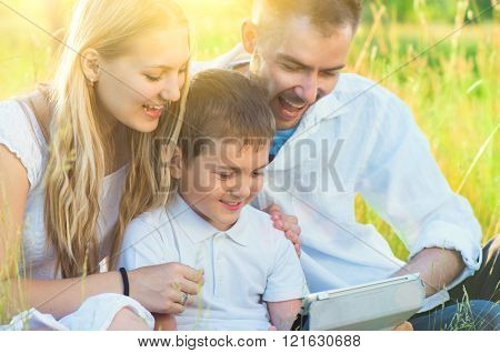 Happy Young Family with kid using Tablet PC in summer park. Dad, Mom and little boy with computer resting outdoors together. Summer holidays