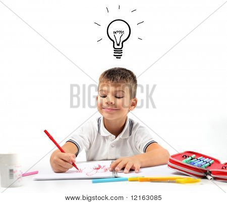 Smiling child having an idea while drawing