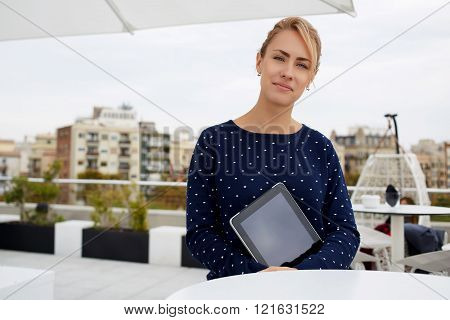 Businesswoman holds touch pad with copy space screen and waits in restaurant meeting with partner