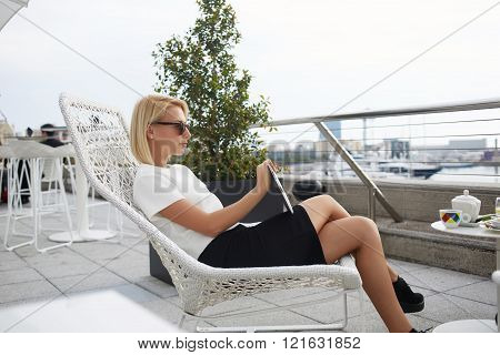 Young stylish female is thinking about something while is resting after seeing movie on touch pad
