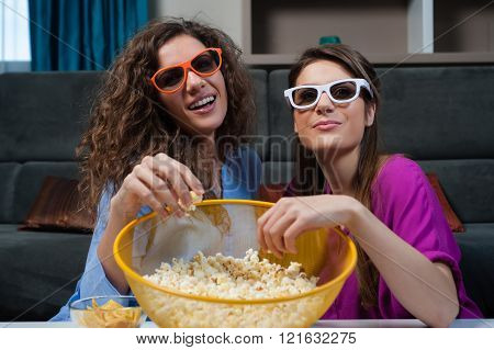 Two smiling girls eating popcorn while watching a movie on tv with 3d glasses.