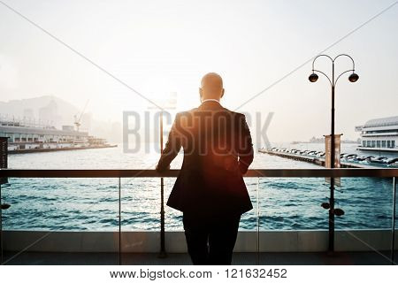 Silhouette of a young successful businessman in black suit is enjoying landscape