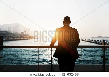 Silhouette of male skilled and confident businessman is thinking about his future plans