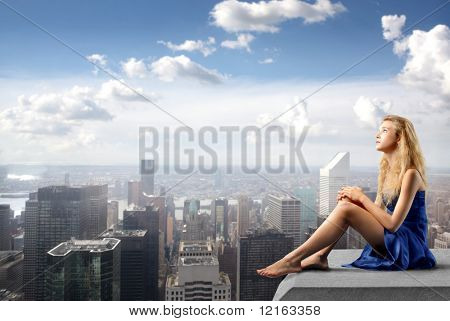 Young woman in elegant dress sitting on the rooftop of a skyscraper