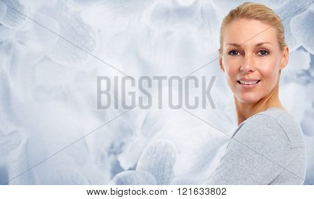 Beautiful woman face over blue abstract background.