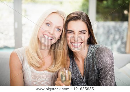 Portrait of beautiful women making funny faces and having champagne flute