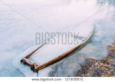 Frozen into ice of river, lake, pond old wooden boat. Forsaken r