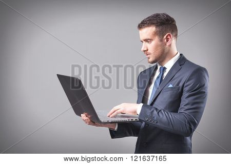 Handsome businessman holding a laptop on grey background