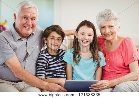 Portrait of senior couple and their grand children using digital tablet in living room