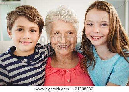 Portrait of grandmother and grandchildren sitting together on sofa in living room