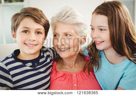 Grandmother and grandchildren sitting together on sofa in living room
