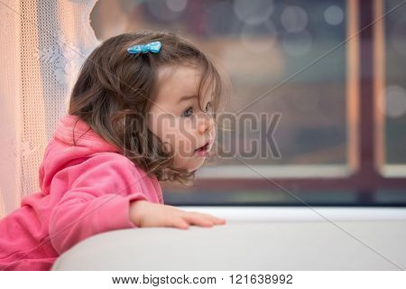 Little girl with long hair at the window