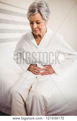 Senior woman suffering from stomach ache sitting on bed in bedroom