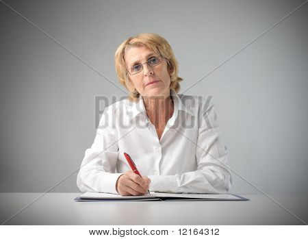 Senior businesswoman writing on a register