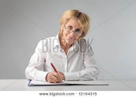 Smiling businesswoman writing on a register