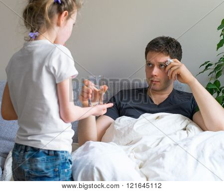 Little girl caring about het sick father.